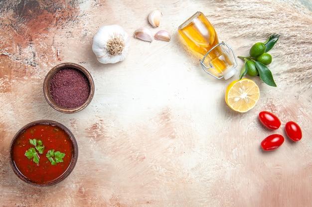 Bovenaanzicht saus knoflook tomaten citroen fles oliesaus kruiden lepel