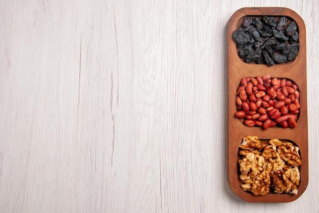 Bovenaanzicht schalen met noten schalen met verschillende noten aan de rechterkant van de witte tafel