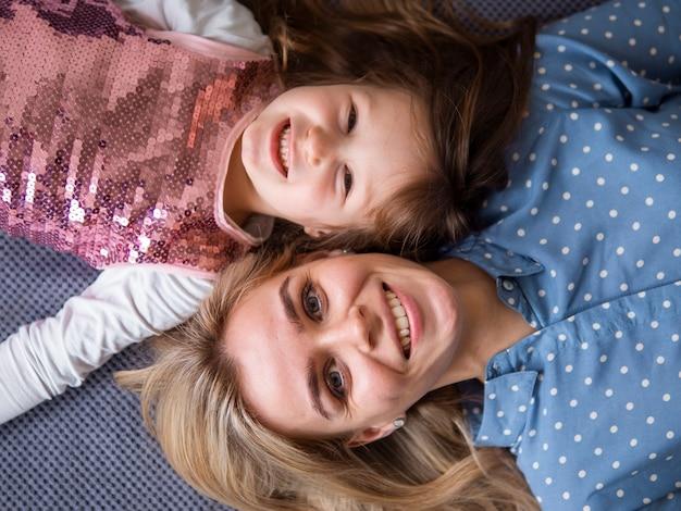 Bovenaanzicht schattig jong meisje en moeder glimlachen