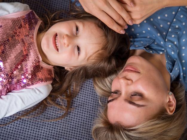 Bovenaanzicht schattig jong meisje en moeder samen