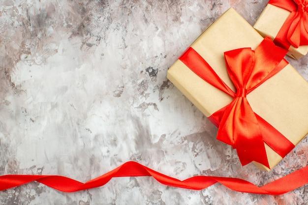 Bovenaanzicht schattige liefde aanwezig in pakket met rode strik op lichte ondergrond