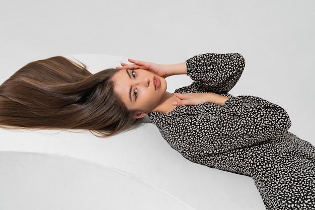Bovenaanzicht schoonheid portret van modieuze vrouw met lange haren in stijlvolle herfst jurk ligt.