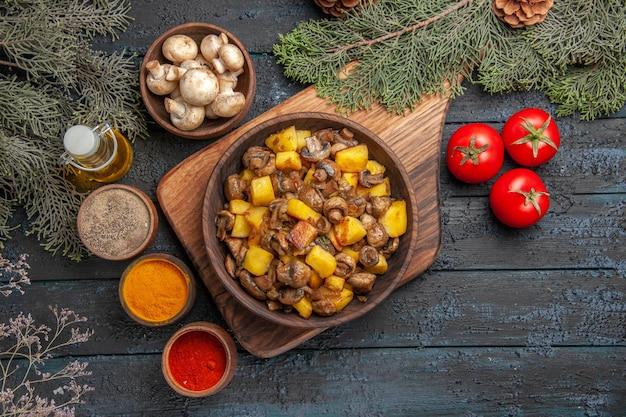 Bovenaanzicht schotel en groenten plaat van aardappelen met champignons op houten bord naast drie tomaten en kleurrijke kruiden onder olie in fles boomtakken en kom met champignons
