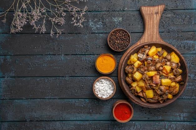 Bovenaanzicht schotel en kruiden een gerecht van aardappelen en champignons op de snijplank en een notitieboekje en kleurrijke kruiden eromheen