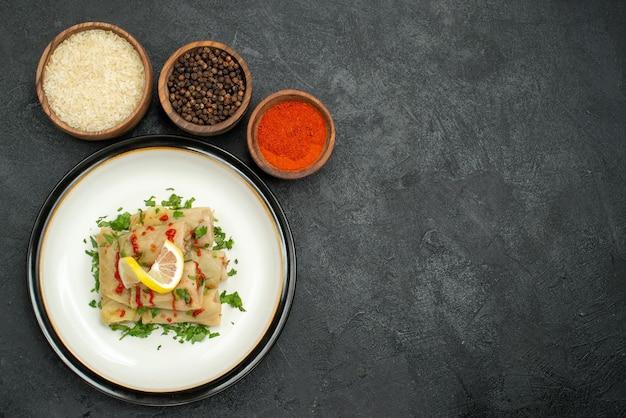 Bovenaanzicht schotel en kruiden gevulde kool met saus citroen en kruiden en kommen kleurrijke kruiden rijst en zwarte peper aan de linkerkant van houten tafel