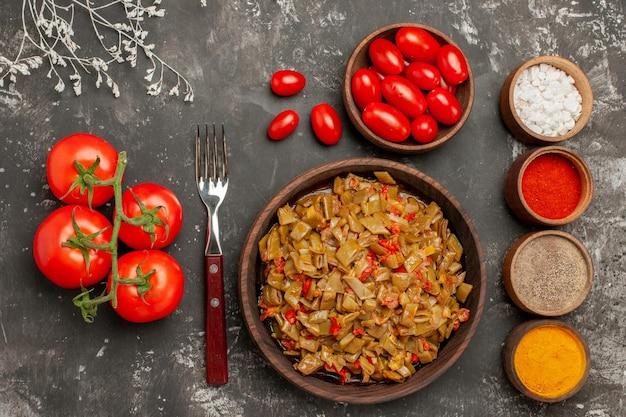 Bovenaanzicht schotel en kruiden tomaten met steeltjes plaat van sperziebonen vork en kleurrijke kruiden op de zwarte tafel