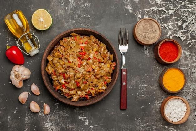 Bovenaanzicht schotel en kruiden vork plaat van sperziebonen knoflook tomaten paprika vier kommen kruiden en fles olie