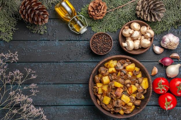 Bovenaanzicht schotel en kruidenplaat van champignons en aardappelen onder de fles oliekom met champignons en de sparren takken met kegels naast knoflook-ui-tomaten