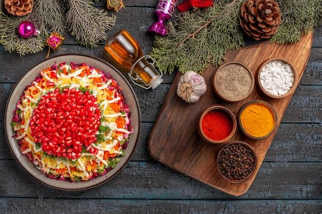 Bovenaanzicht schotel en kruidenschotel met granaatappels naast de fles olie kruiden knoflook op de snijplank en boomtakken met kegels en kerstboomspeelgoed