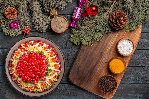 Bovenaanzicht schotel en kruidenschotel met granaatappels naast de kruiden op de snijplank en boomtakken met kegels en kerstboomspeelgoed