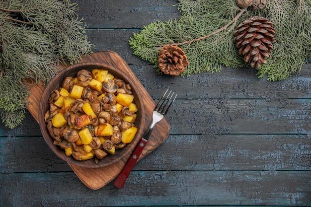 Bovenaanzicht schotel en snijplank schotel van champignons en aardappelen naast vork en snijplank onder sparren takken met kegels