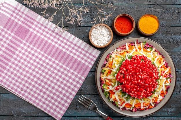 Bovenaanzicht schotel en tafelkleed kleurrijke kruiden schotel van granaatappel wortel aardappel naast de vork boomtakken en roze-wit geruit tafelkleed
