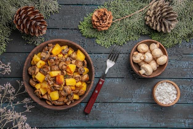 Bovenaanzicht schotel en takken plaat van champignons en aardappelen op de grijze tafel onder de vuren takken met kegels naast de vork champignons en zout