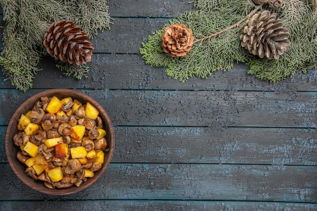 Bovenaanzicht schotel en takken schotel van champignons en aardappelen aan de linkerkant van de grijze tafel onder de sparren takken