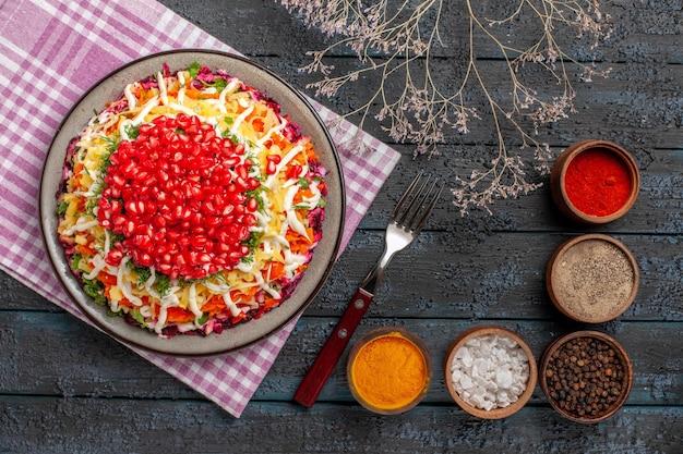 Bovenaanzicht schotel en vork smakelijk gerecht op het geruite tafelkleed naast de kommen met kruidentakken en vork op de grijze tafel