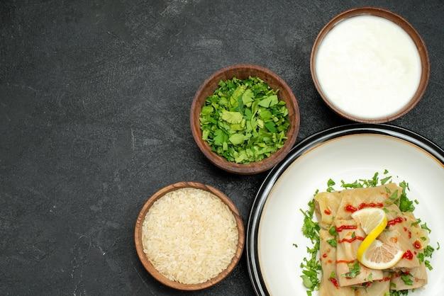 Bovenaanzicht schotel gevulde kool met kruiden citroen en saus op witte plaat en kommen met rijst kruiden en zure room op zwarte tafel