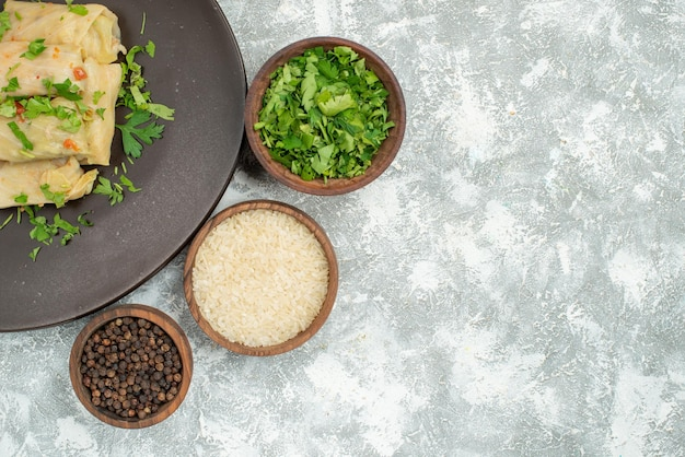 Bovenaanzicht schotel in bord gevulde kool in bord naast de kom met kruidenrijst en zwarte peper aan de linkerkant van grijze tafel