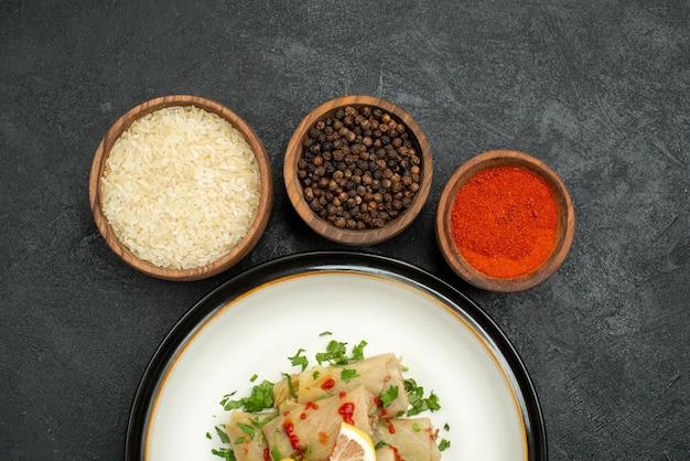 Bovenaanzicht schotel met kruiden smakelijk gevulde kool met kruiden citroen en saus en kommen kleurrijke kruiden rijst en zwarte peper op donkere ondergrond