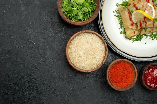 Bovenaanzicht schotel met saus witte plaat van gevulde kool met citroen kruiden en saus en specerijen rijst kruiden en saus in kommen aan de rechterkant van donkere tafel