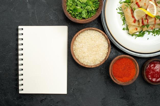 Bovenaanzicht schotel met saus witte plaat van gevulde kool met citroen kruiden en saus en specerijen rijst kruiden en saus in kommen naast wit notitieboekje op donkere ondergrond