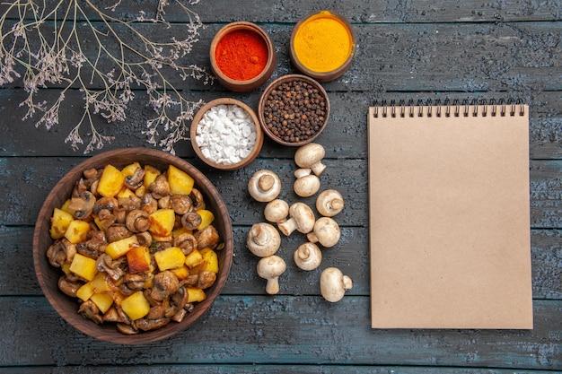 Bovenaanzicht schotel notitieboekje en kruiden schotel van champignons en aardappelen naast witte champignons kleurrijke kruiden takken en een notitieboekje