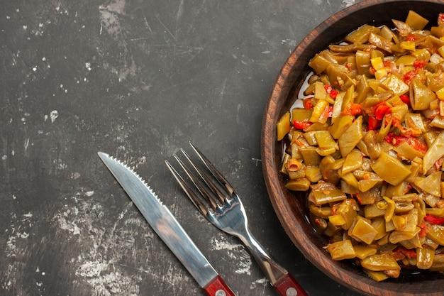 Bovenaanzicht schotel op de tafelplaat van de smakelijke sperziebonen en tomaten naast de vork en het mes op de donkere tafel