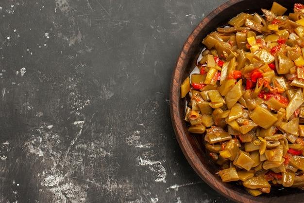 Bovenaanzicht schotel op het tafelbord van de smakelijke sperziebonen en tomaten op de donkere tafel