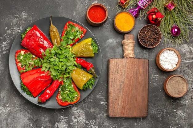 Bovenaanzicht schotel paprika met kruiden houten plank specerijen kerstboom speelgoed