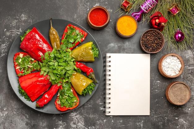 Bovenaanzicht schotel paprika met kruiden witte notebook kruiden kerstboom speelgoed