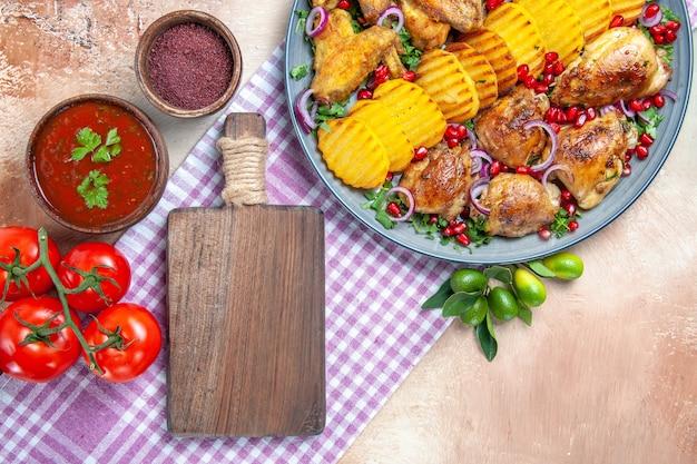 Bovenaanzicht schotel saus kruiden tomaten kip met aardappelen de snijplank