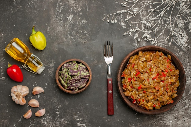 Bovenaanzicht schotel van bonen knoflook paprika olie in fles naast de sperziebonen vork en bord sperziebonen en tomaten op tafel