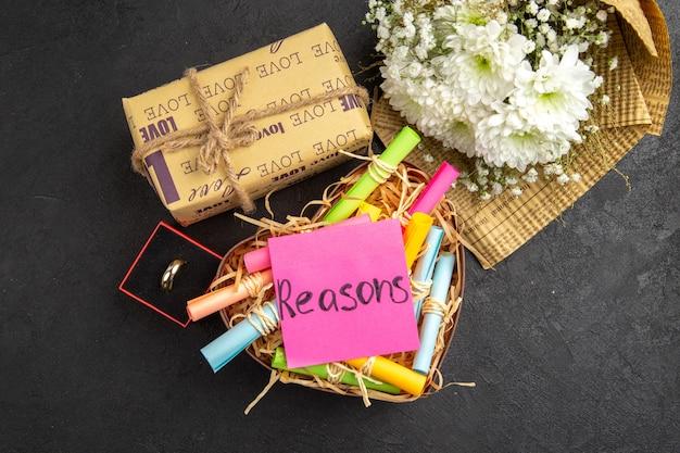 Bovenaanzicht scroll wenspapieren in doos bloemboeket ring op tafel huwelijksaanzoek concept