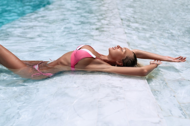 Bovenaanzicht seksueel figuur in een roze bikinivorm sportief bij het blauwe zwembad