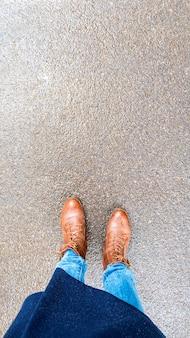 Bovenaanzicht selfie van vrouw voeten in bruine herfst laarzen op een nat asfalt na regen.