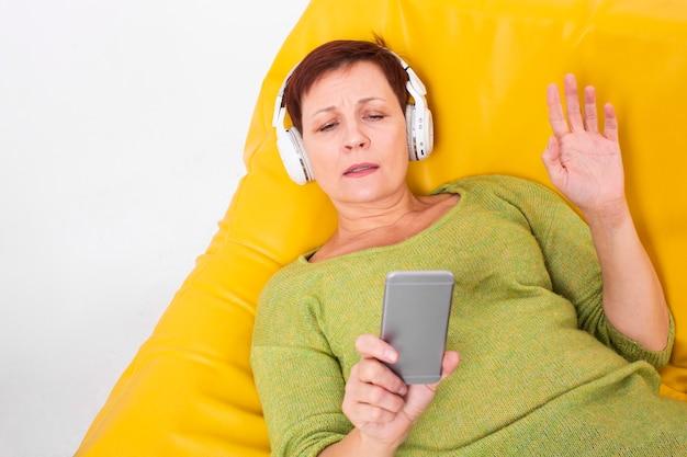 Bovenaanzicht senior vrouwelijke luisteren muziek