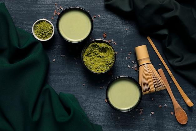 Bovenaanzicht set groene thee poeder naast traditionele gebruiksvoorwerpen
