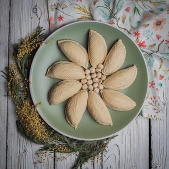 Bovenaanzicht shekerbura met noten en mimosa bloemen in ronde plaat