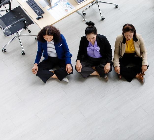 Bovenaanzicht shot van drie aziatische vrouwelijke zakenvrouwen officieren van middelbare leeftijd in formeel pak zittend gehurkt stil op de vloer, dichte ogen samen mediteren aan de tafel van het kantoorwerkstation in gezelschap.