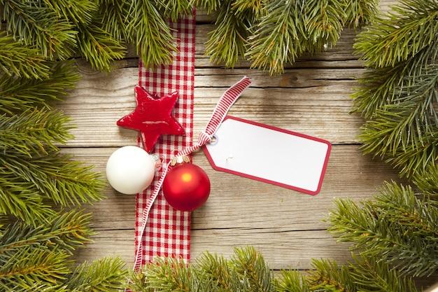 Bovenaanzicht shot van een kerstkaart met een lint en ornamenten omgeven door kerstboomtakken
