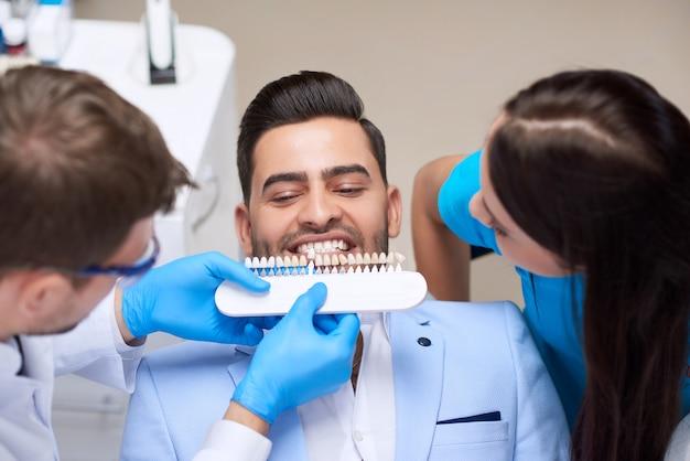 Bovenaanzicht shot van een professionele tandarts wirking met de hulp van de verpleegster die perfect bijpassende kleur van implantaten kiest voor zijn mannelijke patiënt tanden geneeskunde gezondheidszorg whitening kunstgebitten.