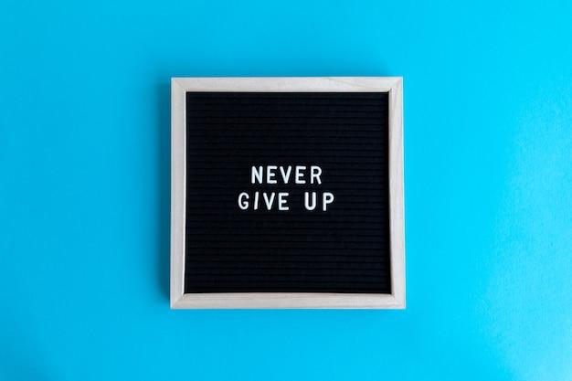 Bovenaanzicht shot van een schoolbord met een nooit opgeven massage op een blauwe achtergrond