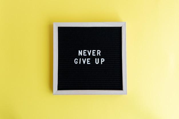 Bovenaanzicht shot van een schoolbord met een nooit opgeven massage op een gele achtergrond