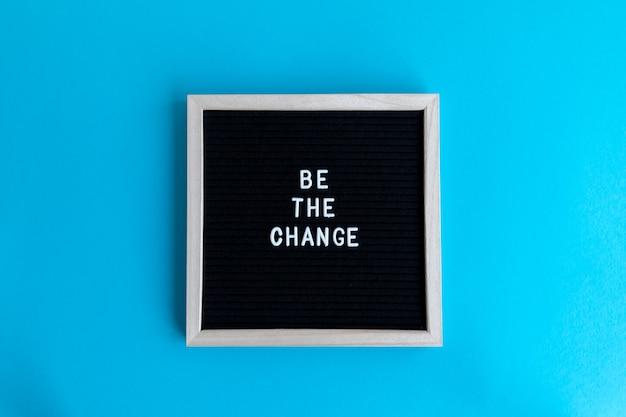 Bovenaanzicht shot van een schoolbord met een wit frame met een be the change massage op een zwarte achtergrond