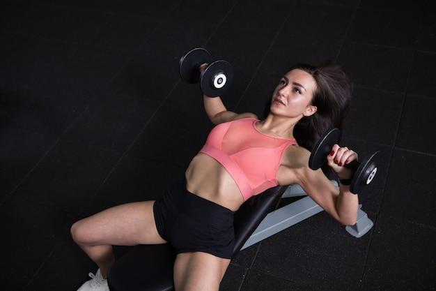 Bovenaanzicht shot van een vrouwelijke bodybuilder die bankdrukken doet met halters