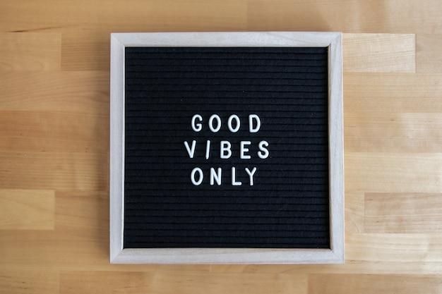 Bovenaanzicht shot van een zwart leeg bord op een houten tafel met alleen een quote van goede vibes