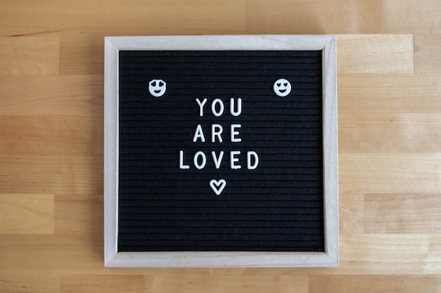 Bovenaanzicht shot van een zwart leeg bord op een houten tafel met je geliefde citaat