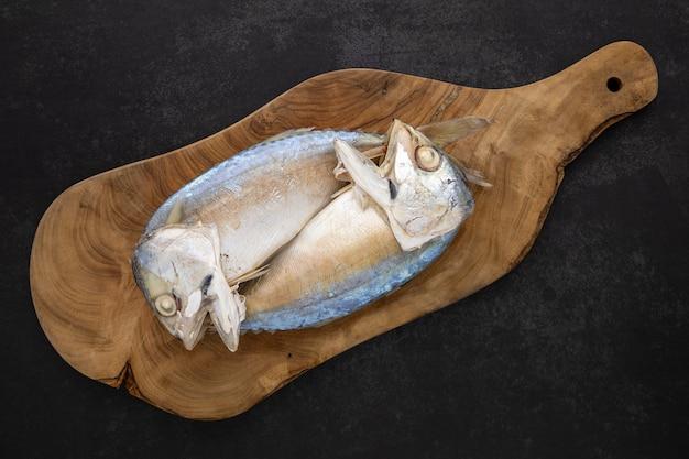 Bovenaanzicht shot van gestoomde makreel in olijf natuurlijke houten snijplank op de donkere toon textuur achtergrond