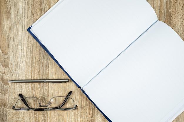 Bovenaanzicht shot van lege lege notebook dagboek en bril met zilveren pen op houten tafel