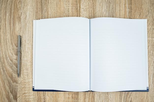 Bovenaanzicht shot van lege lege notebook dagboek met zilveren pen op houten tafel