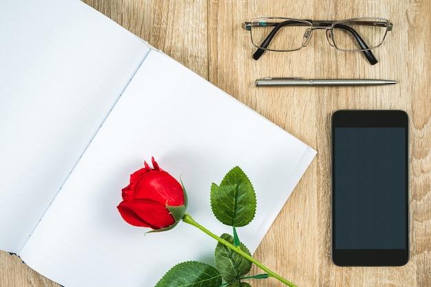 Bovenaanzicht shot van rode rozen lege lege notebook dagboek en bril met smartphone op houten tafel, valentine concept